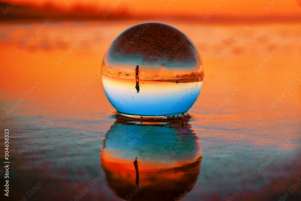 Fototapeta Beautiful selective focus shot of a crystal ball reflecting the breathtaking sunset