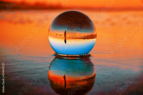Fototapeta Beautiful selective focus shot of a crystal ball reflecting the breathtaking sunset obraz