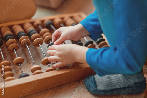 Fotografia, Obraz children's hands count on wooden abacus