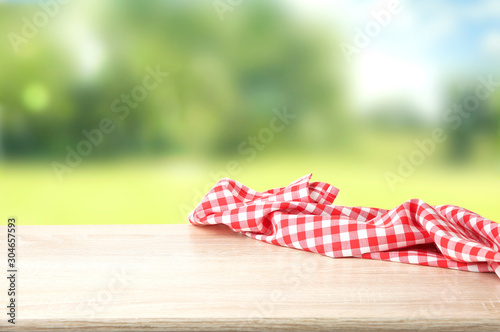 Fotografie, Obraz Red checkered picnic cloth on wooden table empty space background