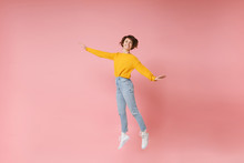 Smiling Young Brunette Woman Girl In Yellow Sweater Posing Isolated On Pastel Pink Background In Studio. People Lifestyle Concept. Mock Up Copy Space. Having Fun Spreading Hands Rising Hands, Jumping.