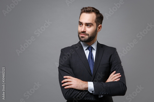 Fototapeta Handsome young business man in classic black suit shirt tie posing isolated on grey background. Achievement career wealth business concept. Mock up copy space. Holding hands crossed, looking aside. obraz na płótnie