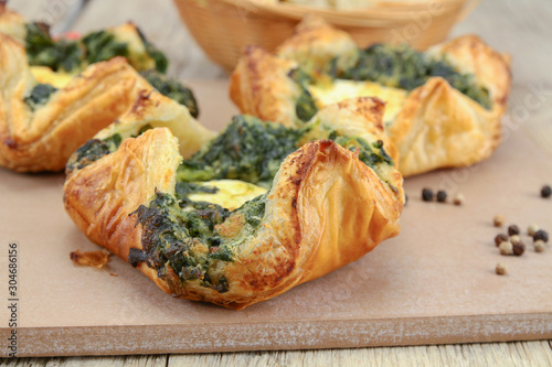 Photo puff pastry with goat cheese and spinach on a chopping board