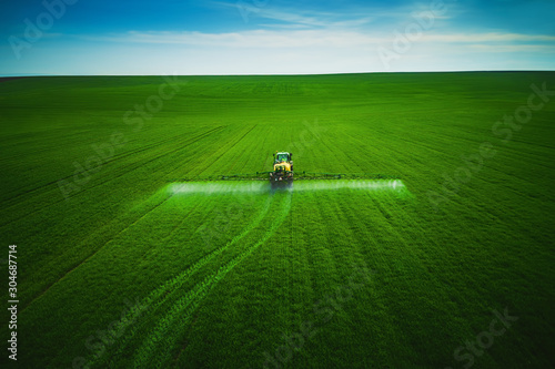 Leinwand Poster Aerial view of farming tractor plowing and spraying on field