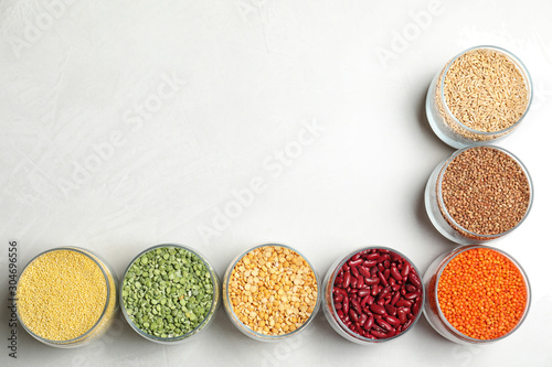 Jars with different cereals on white background, flat lay. Space for text