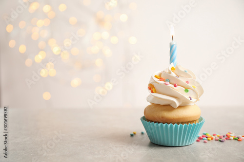 Birthday cupcake with candle on light grey table against blurred lights Canvas Print