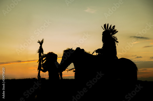 Fototapeta The Indians are riding a horse and spear ready to use In light of the Silhouette