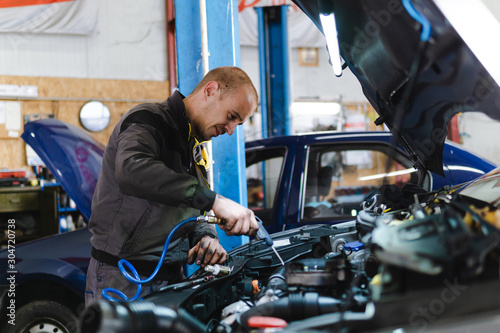 fototapeta na drzwi i meble Handsome mechanic in uniform is working in auto service garage. Repair service.