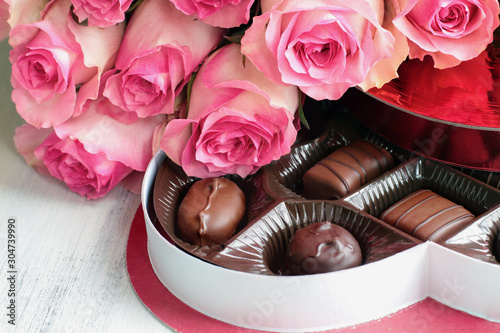 obraz lub plakat Dozen soft colored long stem pink rose flowers with a heart shaped box of chocolate candy for Valentine Day over a wood background.