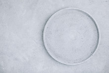 Empty Round Stone Plate On Gray Concrete Background, Top View