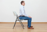 caucasian man sitting on the edge of chair in correct  posture