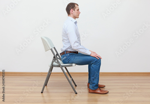 Obraz caucasian man sitting on the edge of chair in correct  posture - fototapety do salonu