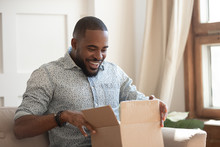 Happy Biracial Man Feel Excited Unpacking Delivery Package