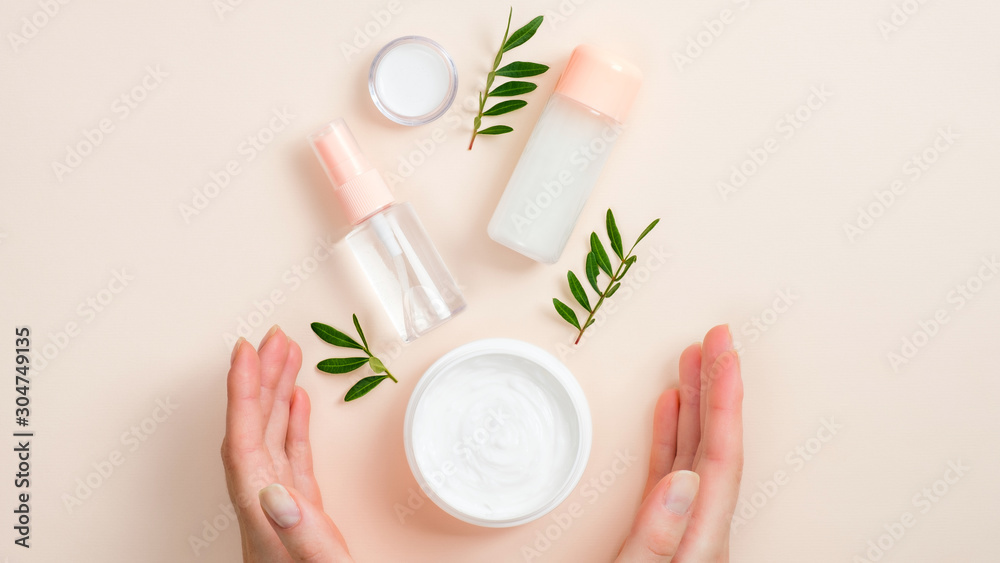 Fototapeta Jar of organic hand cream, essential oils bottle and green leaves on beige background. Skin care, organic natural beauty products concept