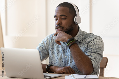 Concentrated biracial man in headphones watching webinar on laptop Canvas Print