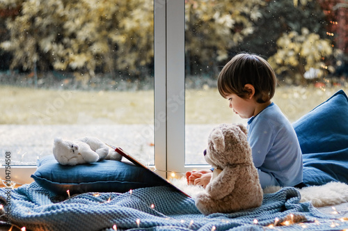 Cute little boy reading book with his teddy bear toy sitting cozy on pillows and knitted blanket near wet window with autumn garden at background Fototapet
