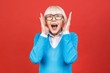 Leinwanddruck Bild - Old adult blonde glad excited cheerful astonished lady smiling, laughing, screaming, raising hands to cheeks, opened mouth, isolated over red background.