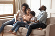 Cheerful mixed-race family with kids using tablet computer