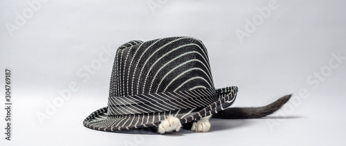 Photo black and white kitten stuck his paw out from under the striped hat