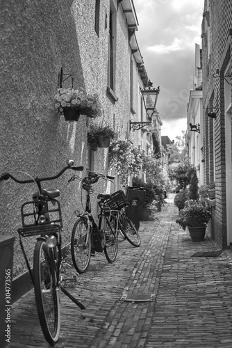 Fotografía  Vertical gray scale shot of bicycles on a beautiful pavement by old buildings