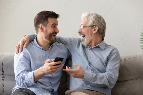 Obraz Happy old father and son having fun, using phone together - fototapety do salonu