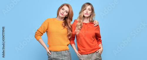 Fotografie, Tablou  Two easy-going happy hipster Woman smiling, Stylish fashion orange colored outfit