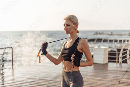 Sport woman kickboxer with bandaged hands in bandages and skipping rope posing on the beach Wallpaper Mural