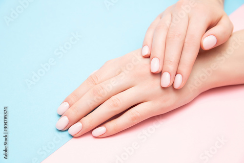 Stampa su Tela Beautiful female hands with stylish nail manicure gel polish on pink and blue background, top view