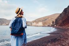 Tourist Walking On Red Beach By Aegean Sea In Akrotiri, Santorini Island, Greece. Woman With Backpack Traveling