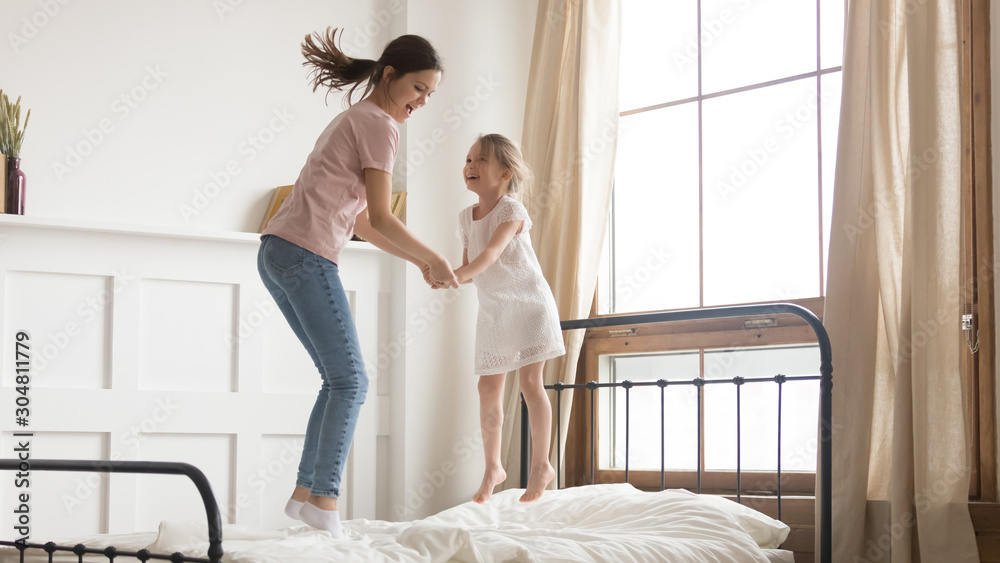 Fototapety, obrazy: Playful mom have fun jumping on bed with little daughter
