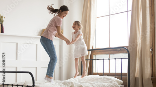 Obraz Playful mom have fun jumping on bed with little daughter - fototapety do salonu