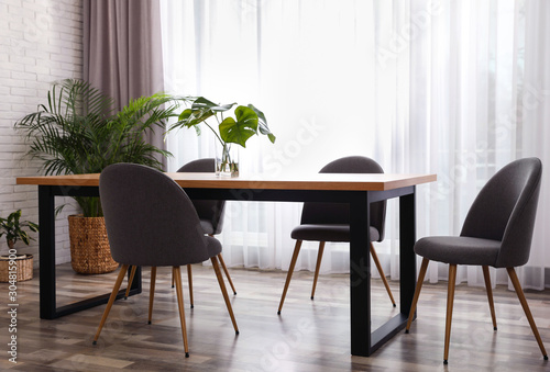 Obraz Fresh leaves of tropical plants on table in room. Home decoration - fototapety do salonu