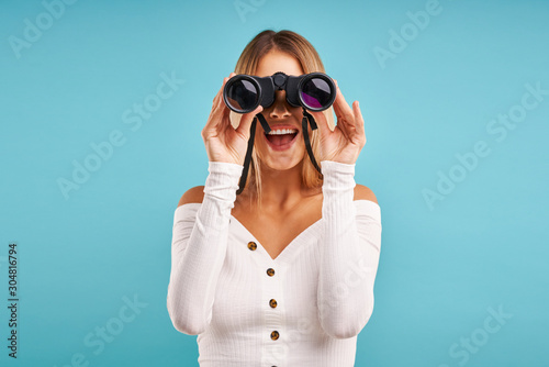 Beautiful adult woman posing over blue background with binoculars Canvas Print