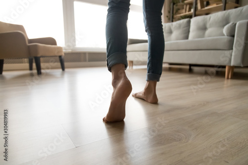 Photo Close up of woman walking barefoot on warm wooden floor