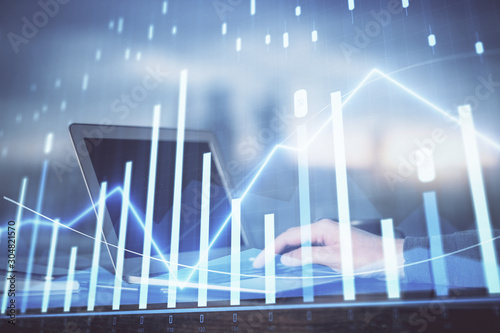 Photo  Double exposure of man's hands writing notes with laptop of stock market with forex graph background
