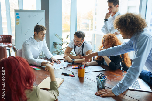 Fototapety, obrazy: 6 employees of both genders at a large and cozy office working actively, airy and light scenery, discussing business people sitting at the large desk surrounded by charts and panoramic windows.