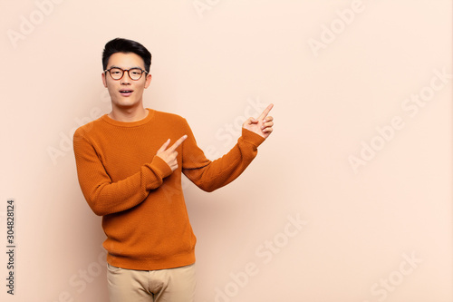 young chinese man feeling joyful and surprised, smiling with a shocked expressio Canvas Print