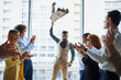Young business leaders celebrate win of their arabian colleague standing in the center in pose of winner, panoramic window background