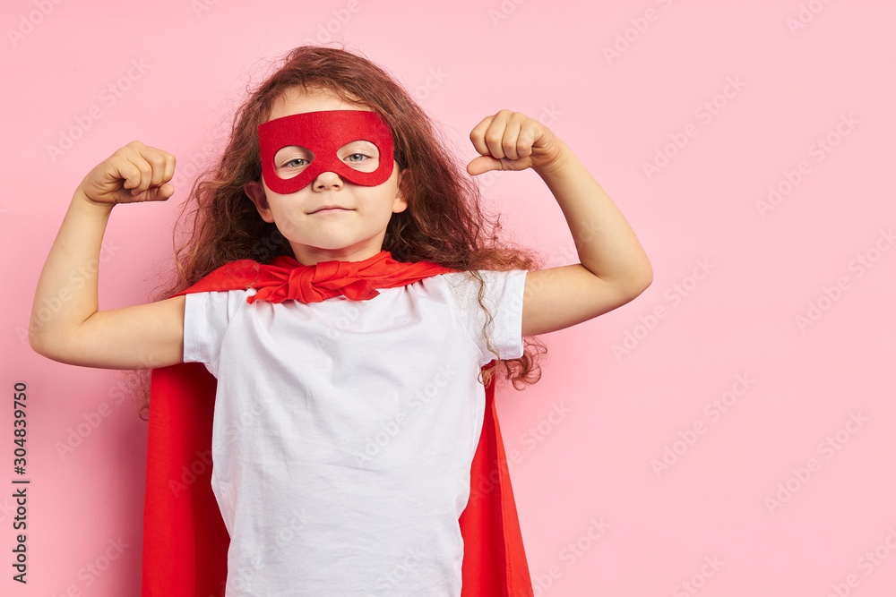 Fototapeta attractive little curly girl wearing red hero suit and mask showing how she is strong isolated over pink background