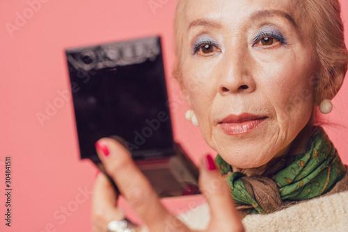 Spoed Fotobehang Aromatische コンパクトで化粧を確認するシニア女性