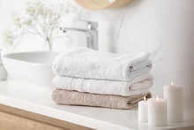Clean Towels And Burning Candles On Counter In Bathroom