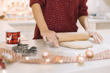 Cropped Woman Rolling Dough On Counter With Christmas Decoration