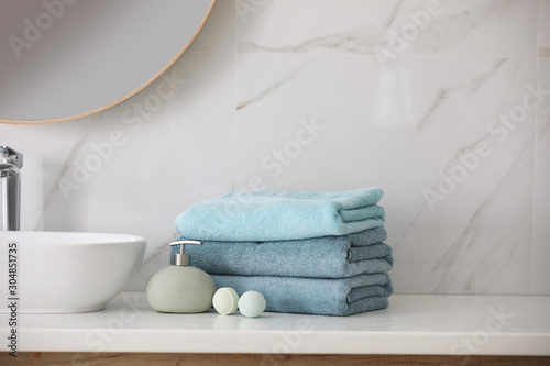 Photo Stack of fresh towels, soap dispenser and bath bombs on countertop  indoors