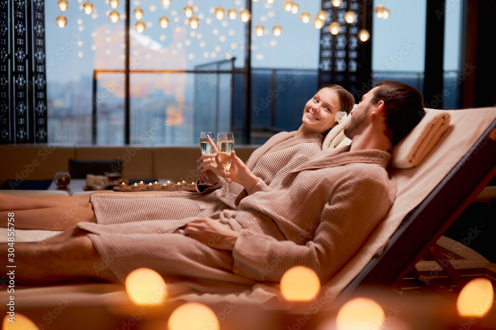 Fototapeta Spa, relax, enjoying concept. Married couple together relaxing in spa salon, lying on beds drinking champagne, using candles