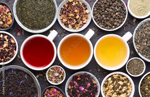 Assortment of tea cups, dried leaves, fruit and herbs in bowls on dark, stone b Fototapete