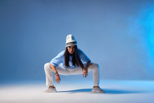 Attractive Young Dancer With Long Straight Brunette Hair, Dressed In Light Coloured Clothes, Sitting On Squat, Putting Hands On Knees, Looking At Camera Ready To Start Performance, Blue Smoke