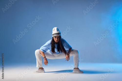 Foto Attractive young dancer with long straight brunette hair, dressed in light colou
