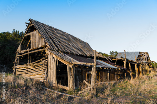 Fototapeta Ruins of an old wooden barn made from rustic logs and planks obraz