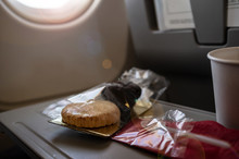 Food Or A Small Snack In An Airplane On The Rear Seat Table, In Economy Class. Baking In Packaging And Coffee In A Plastic Cup, Lit By The Sun, Which Shines Through Window Of An Plane.