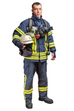 A Young Brave Fireman In A Fireproof Uniform Stands And Looks At The Camera With A Helmet In His Hands.